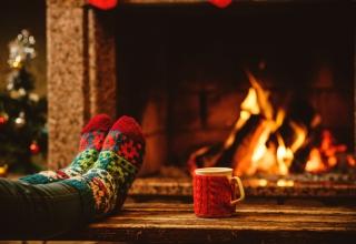 winters plaatje voor de kachel met kerstsokken en kopje warme drank