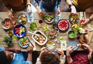 Groep mensen met eten op een tafel