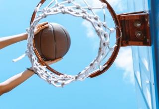 Foto van basketbal die door een korf wordt gegooid