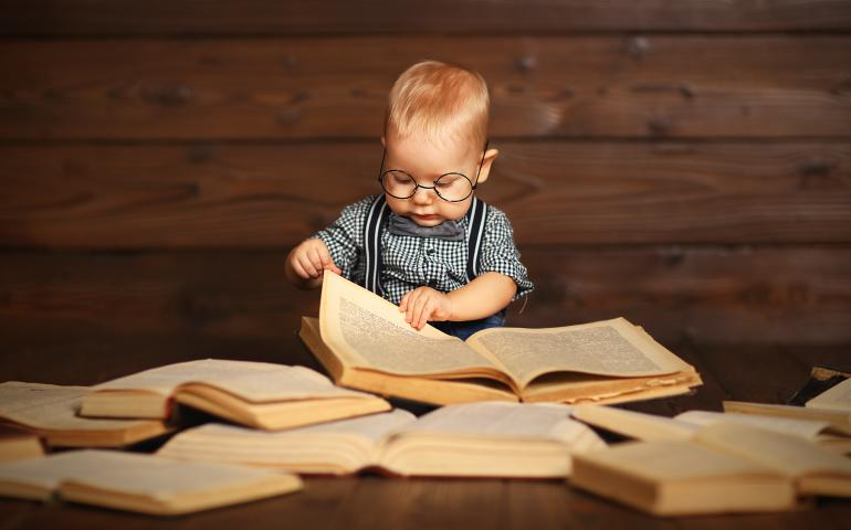 Foto van baby met bril tussen stapel met boeken